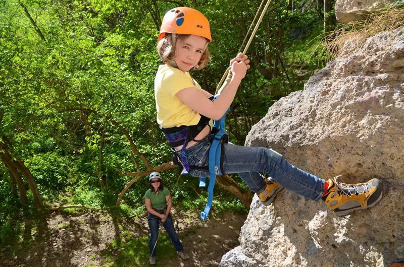Kind klettert am Felsen